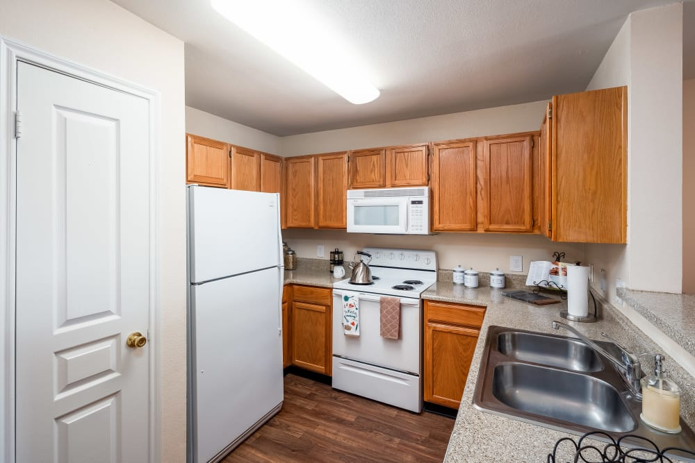 Kitchen with white appliances and double sink and ample storage space at Arbrook Park Apartment Homes in Arlington, Texas