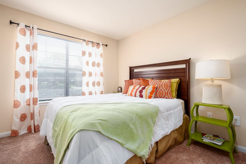 Large windows help to naturally light this comfortable bedroom at Arbrook Park Apartment Homes in Arlington, Texas