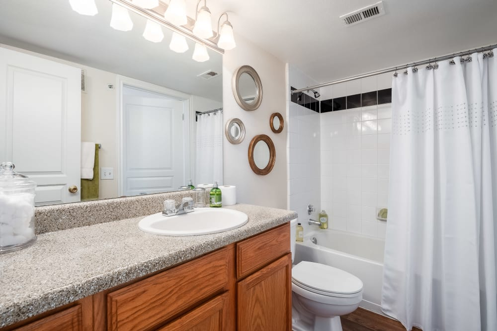 This bathroom features a large vanity mirror and shower bathtub at Arbrook Park Apartment Homes in Arlington, Texas