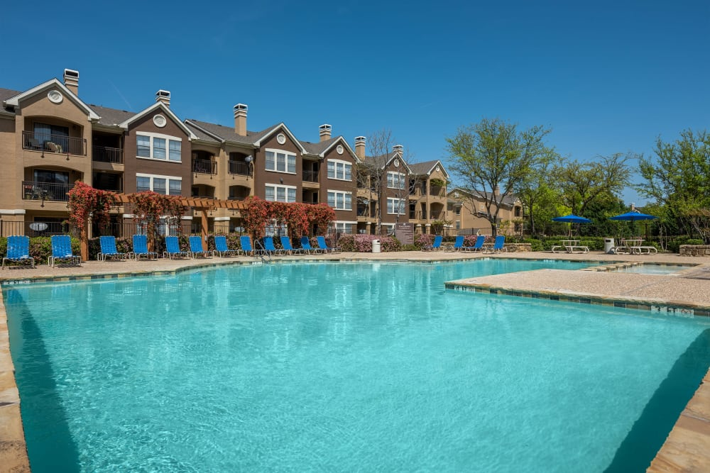 Beautiful community pool with apartments in the background at Arbrook Park Apartment Homes in Arlington, Texas