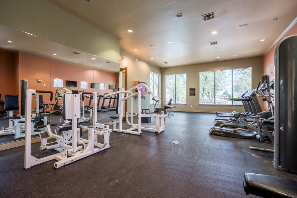 Fitness center is naturally well lit with large windows and high ceiling for good ventilation at Arbrook Park Apartment Homes in Arlington, Texas