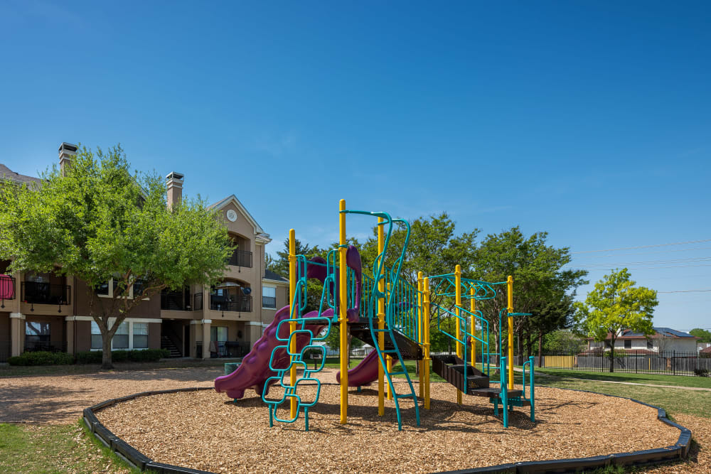 Play ground equipment with bark chips and lots of green space at Arbrook Park Apartment Homes in Arlington, Texas