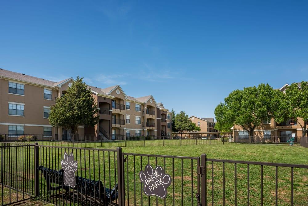 Fenced dog park outside apartments at Arbrook Park Apartment Homes in Arlington, Texas