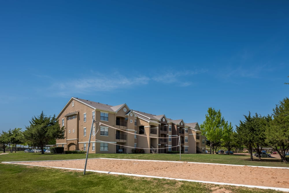 Exterior of apartments in the background with sand volleyball court in the foreground at Arbrook Park Apartment Homes in Arlington, Texas