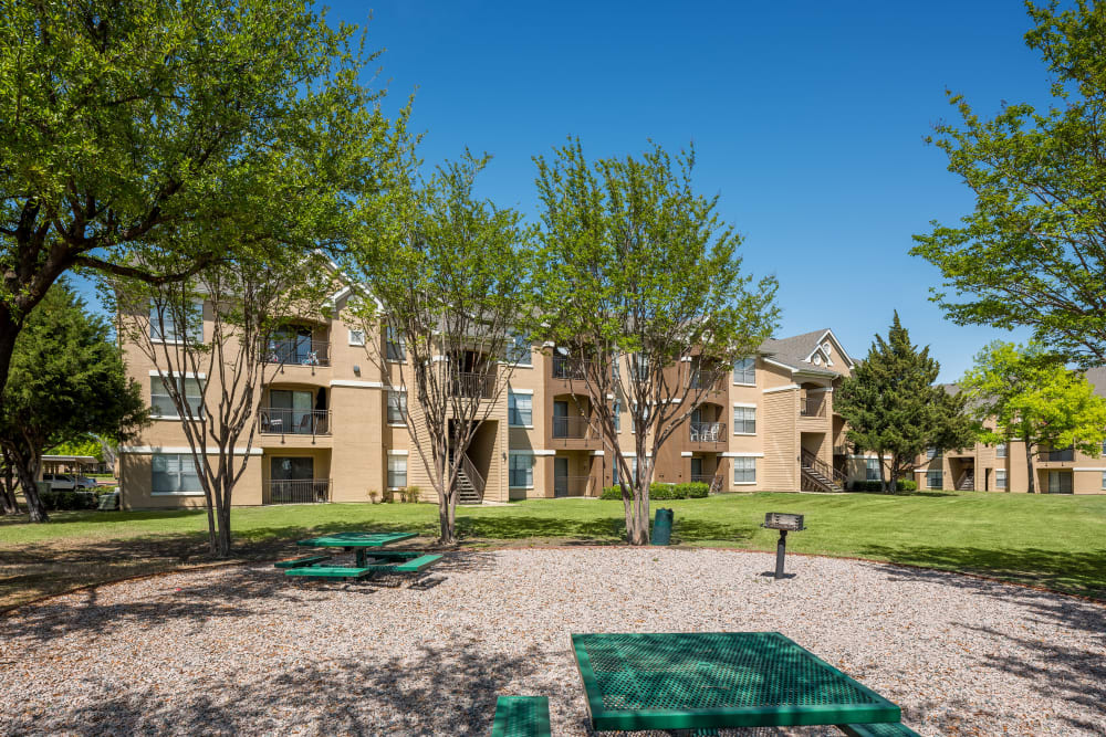 Community picnic and barbecue zone is well shaded by mature trees at Arbrook Park Apartment Homes in Arlington, Texas