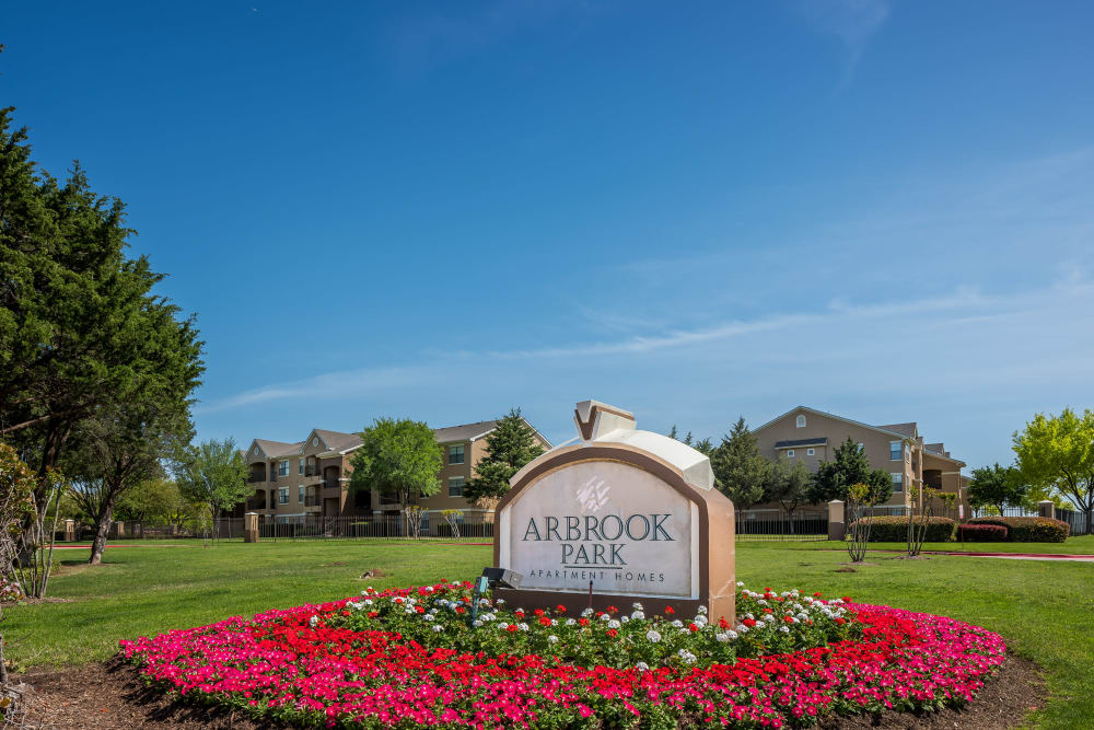 Community sign entryway with lovely flowers at Arbrook Park Apartment Homes in Arlington, Texas