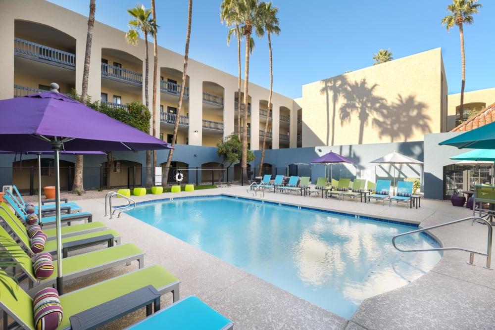 Poolside lounge chairs and umbrellas beside swimming pool at 4127 Arcadia in Phoenix, Arizona