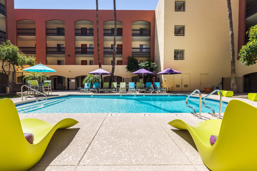 Building exterior and community swimming pool with brightly colored lounge chairs at 4127 Arcadia in Phoenix, Arizona