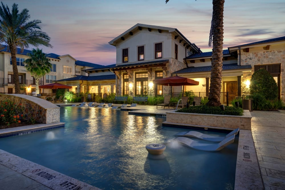 Evening image of clubhouse exterior and swimming pool at Arrabella in Houston, Texas