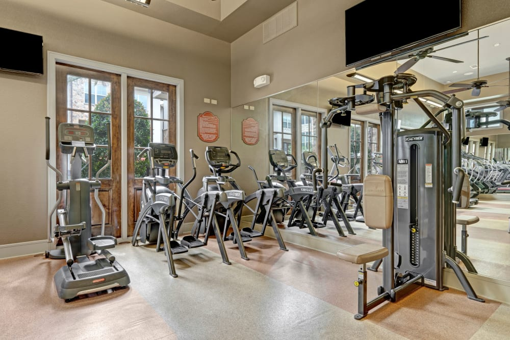 The fitness center features modern equipment and tall ceilings at Arrabella in Houston, Texas