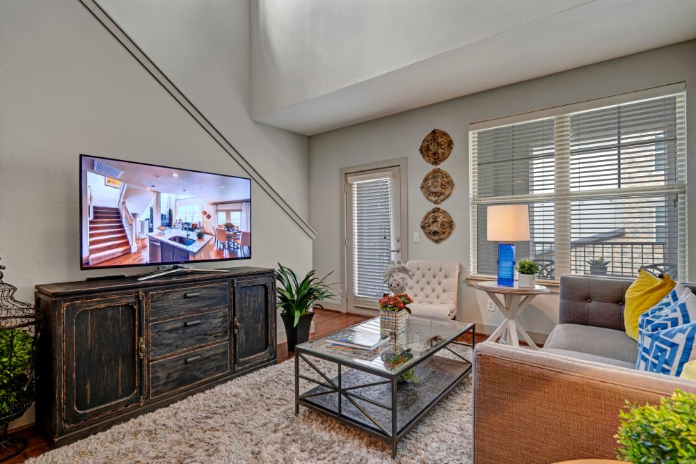 Living room area with TV coffee table and couch seating enjoys vaulted ceiling in an apartment at Arrabella in Houston, Texas