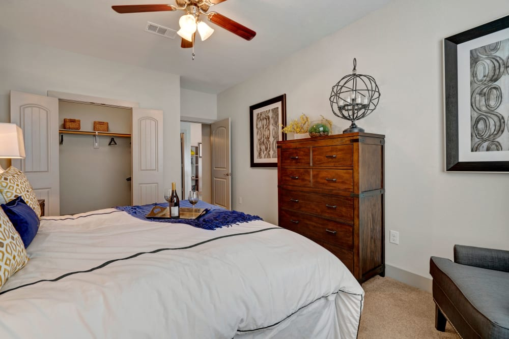 Spacious bedroom with large closet and large wooden hutch features art on the walls