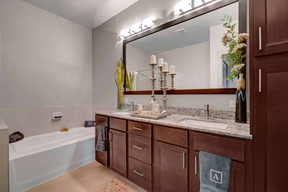 Large vanity mirror in this bathroom that features a bathtub at Arrabella in Houston, Texas