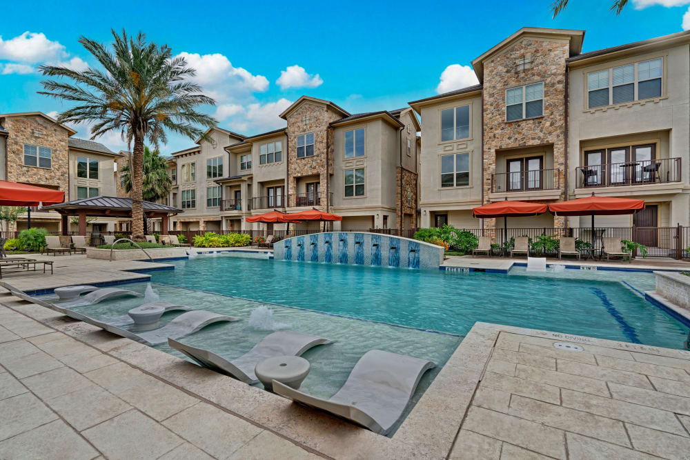 Outdoor community pool featuring lounge chairs and shade umbrellas at Arrabella in Houston, Texas