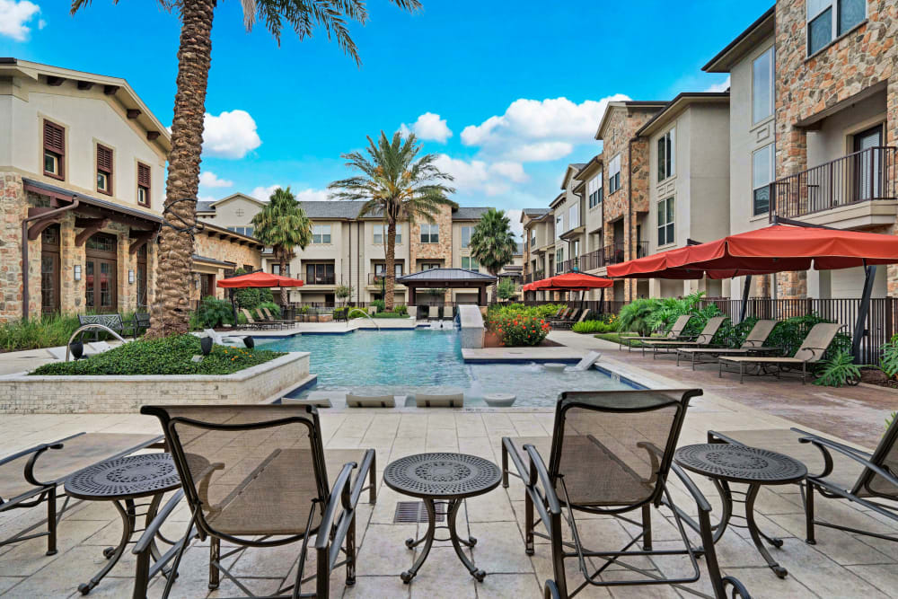Lounge chairs with umbrellas and comfortable seating right next to the community pool at Arrabella in Houston, Texas