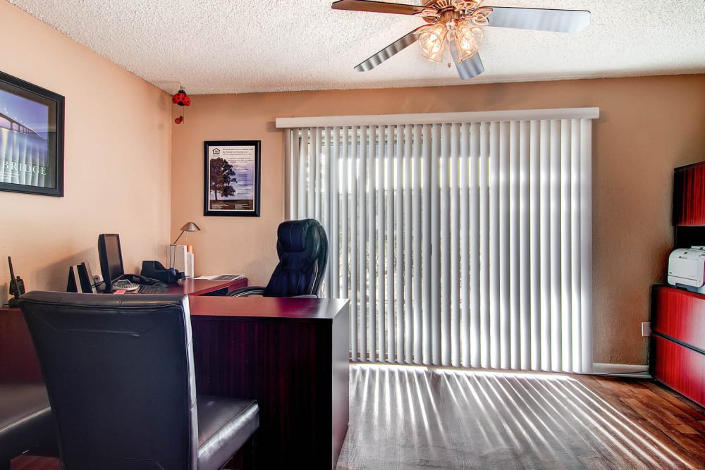 Leasing office desk with sliding glass doors leading outside at Arvada Green Apartment Homes in Arvada, Colorado