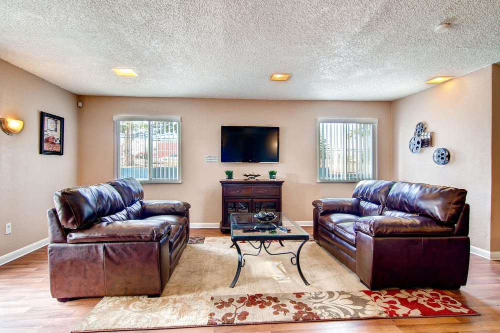 Couches and coffee table offer a comfortable spot to sit in the clubhouse at Arvada Green Apartment Homes in Arvada, Colorado