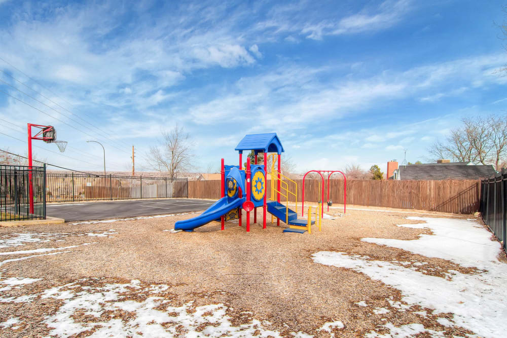 Playground structure surrounded by a grassy area at Arvada Green Apartment Homes in Arvada, Colorado
