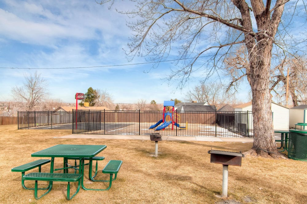 Barbecue and picnic area by green space and playground at Arvada Green Apartment Homes in Arvada, Colorado