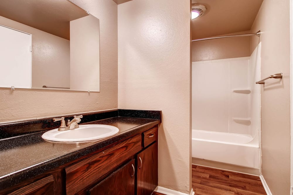 This bathroom featuring a large vanity mirror well finished bathroom sink countertop and a shower bathtub can be found at Arvada Green Apartment Homes in Arvada, Colorado