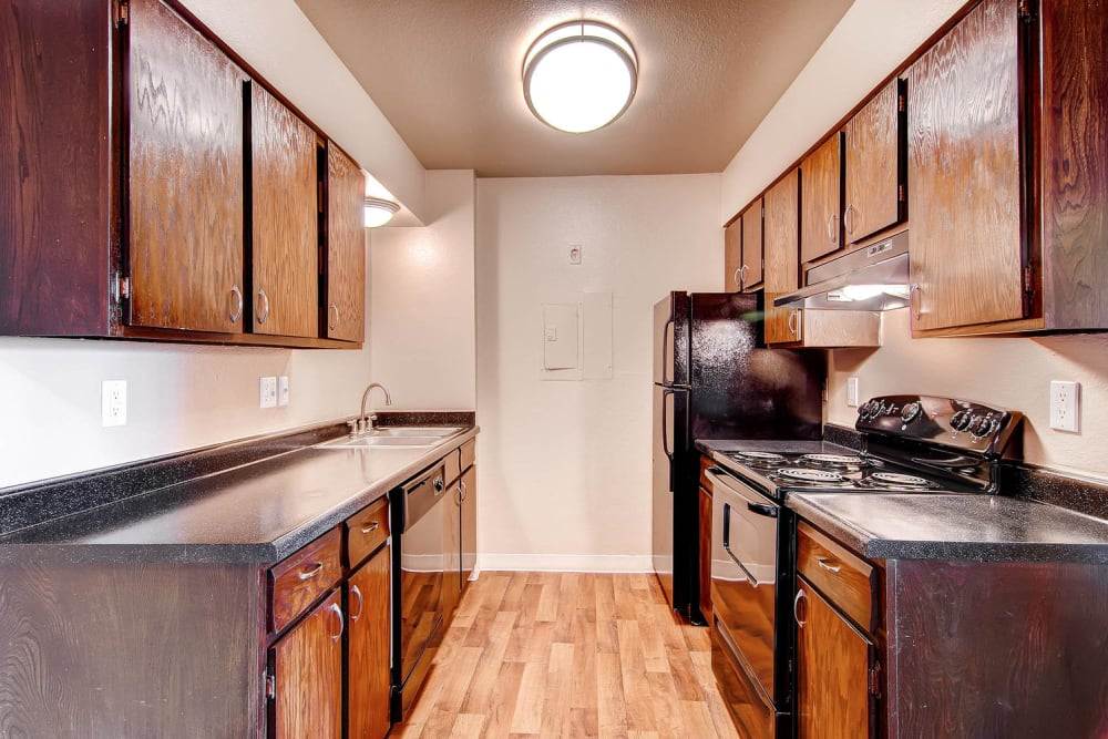 This modern kitchen features lots of storage space and counter surface area in apartment at Arvada Green Apartment Homes in Arvada, Colorado