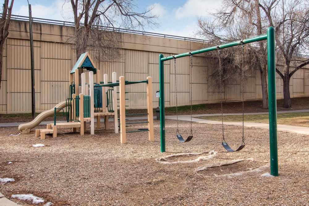 Play ground equipment featuring swings slide and monkey bars at Arvada Village Apartment Homes in Arvada, Colorado