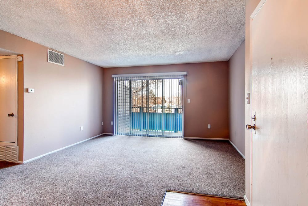 Large spacious living room with sliding door access to outside in an apartment at Arvada Village Apartment Homes in Arvada, Colorado