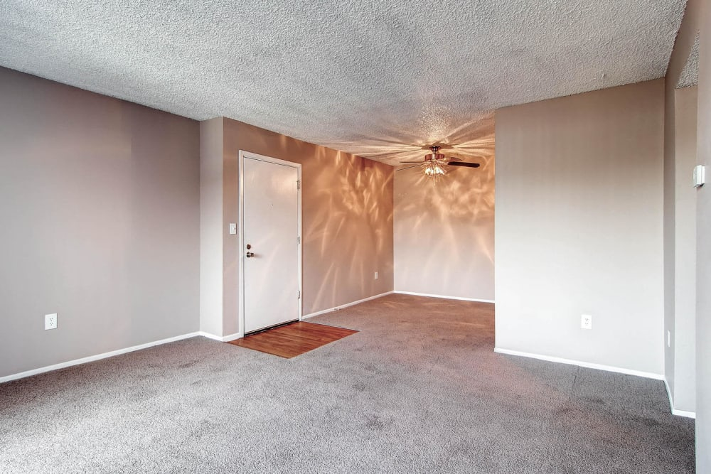 Living room space an apartment entrance off of kitchen and dining room room at Arvada Village Apartment Homes in Arvada, Colorado