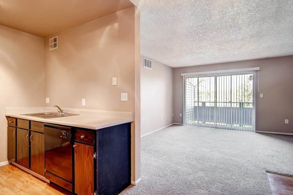Spacious living room off of kitchen and dining area with large sliding doors to outdoor in at Arvada Village Apartment Homes in Arvada, Colorado