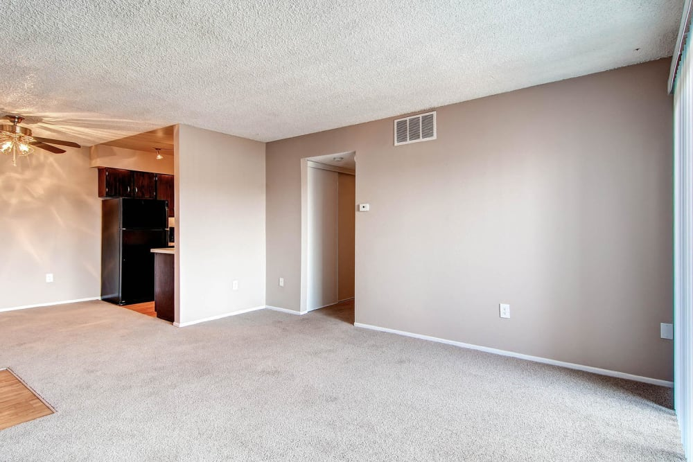 Living room and dining room space off of kitchen in an apartment at Arvada Village Apartment Homes in Arvada, Colorado