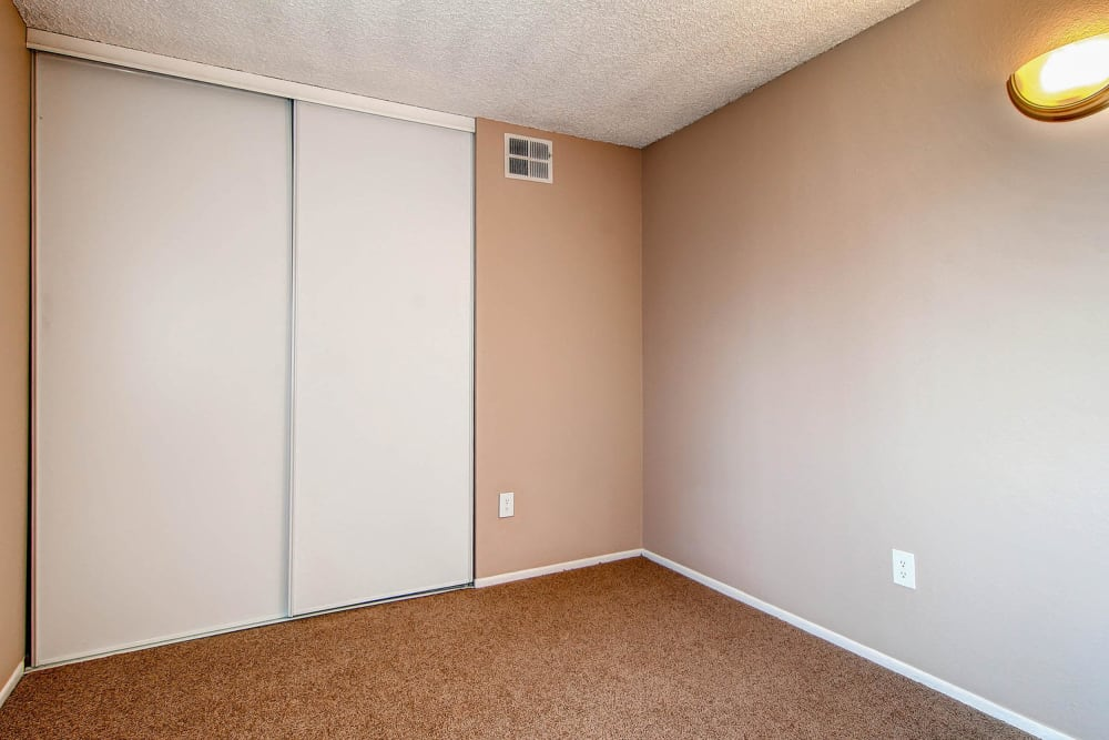 Bedroom with large sliding closet doors at Arvada Village Apartment Homes in Arvada, Colorado