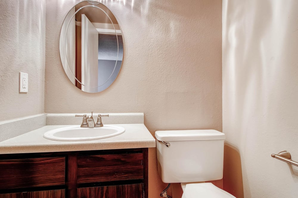 Bathroom featuring an oval mirror and shower bathtub in an at Arvada Village Apartment Homes in Arvada, Colorado