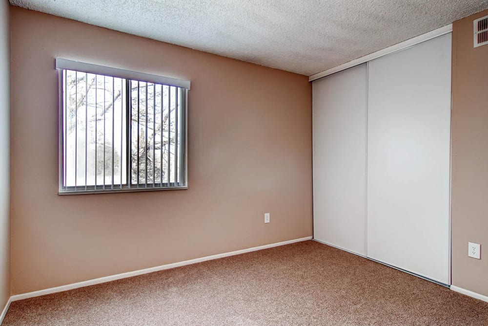Bedroom with sliding door closet in an apartment at Arvada Village Apartment Homes in Arvada, Colorado