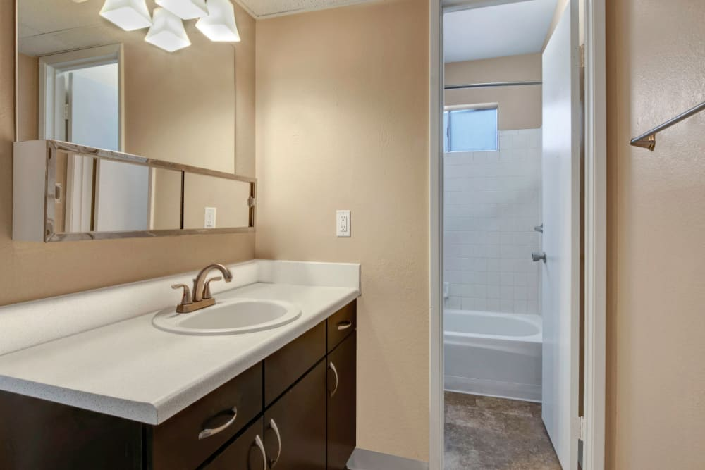 Bathroom featuring large vanity mirror and shower bathtub in an apartment at Avia McCormick Ranch Apartments in Scottsdale, Arizona