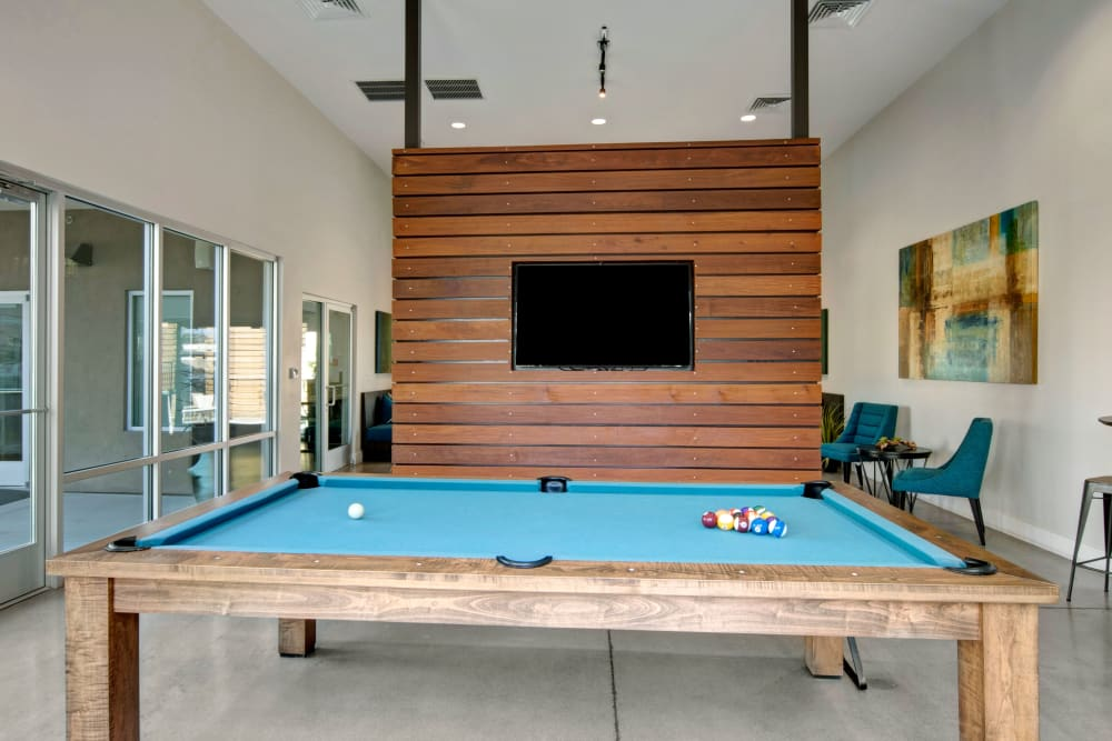 Clubhouse interior featuring a billiards table and large sliding glass doors at Avia McCormick Ranch Apartments in Scottsdale, Arizona