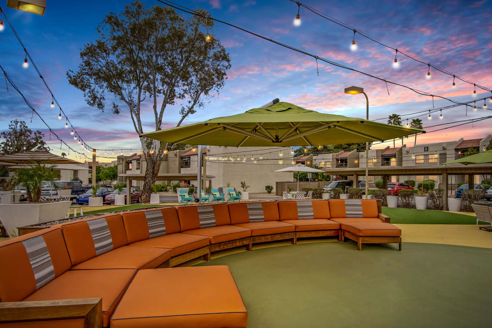 Beautiful sunset with colored clouds in the background and lounge chair couches in the foreground at Avia McCormick Ranch Apartments in Scottsdale, Arizona