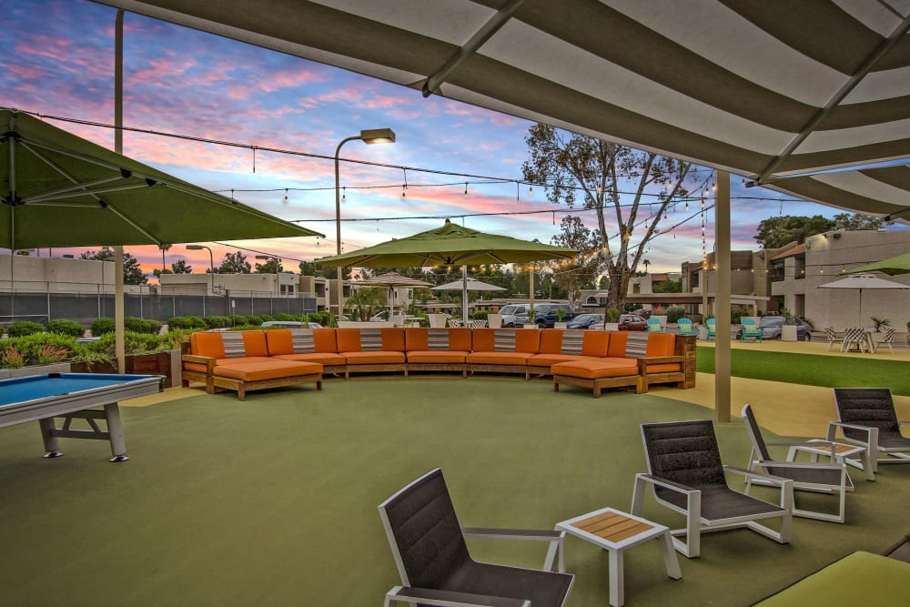 Outdoor patio seating with lounge chairs and tables with a Beautiful sunset and clouds In the distance at Avia McCormick Ranch Apartments in Scottsdale, Arizona