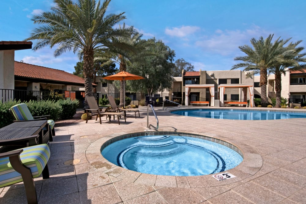 Hot tub spa by community pool with lounge seating at Avia McCormick Ranch Apartments in Scottsdale, Arizona