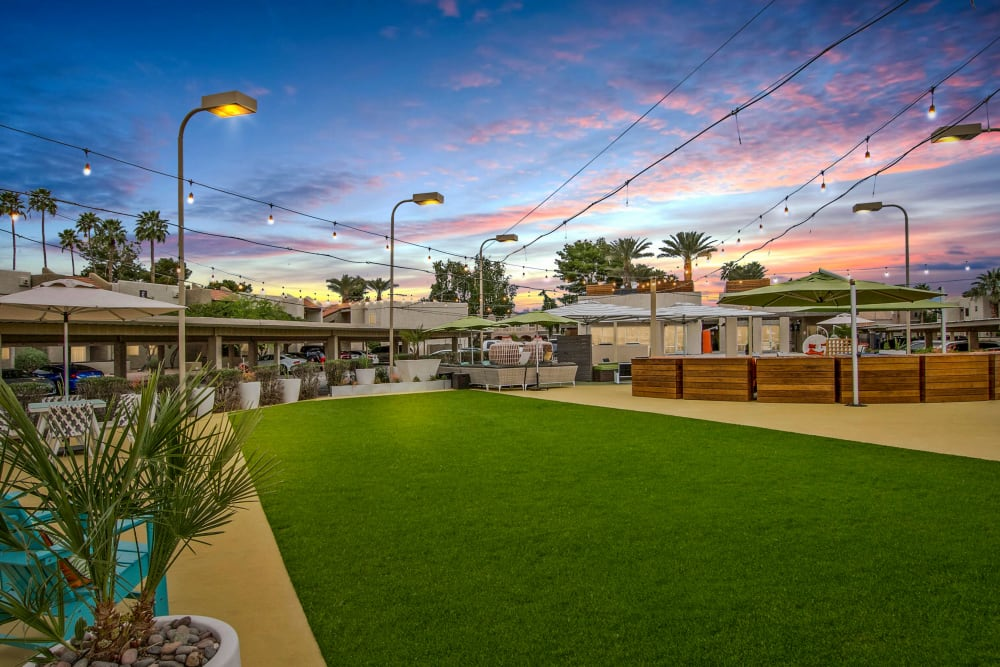 Sun setting with bright colored clouds over the outdoor community space located at Avia McCormick Ranch Apartments in Scottsdale, Arizona