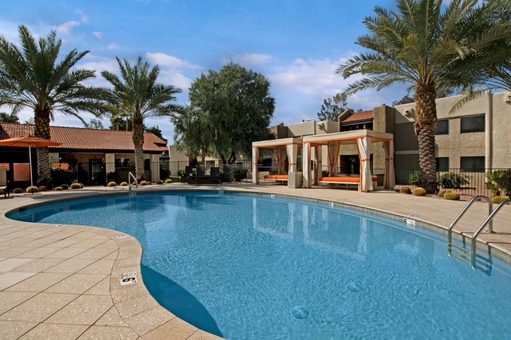Beautiful community swimming pool with gazebos and palm trees in the background at Avia McCormick Ranch Apartments in Scottsdale, Arizona