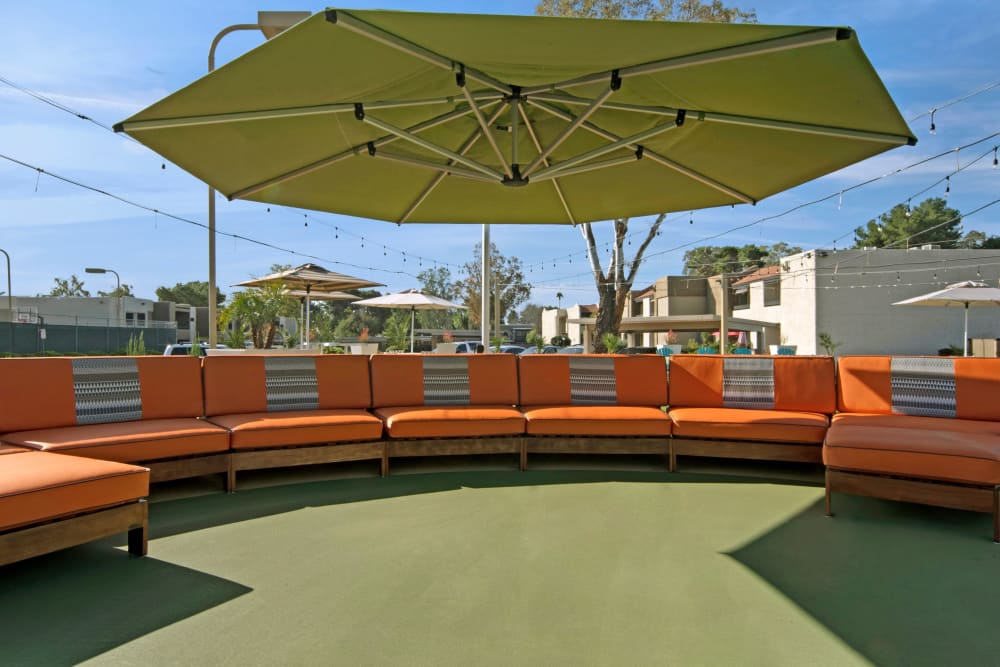 Large shade umbrella and orange community seating area by pool at Avia McCormick Ranch Apartments in Scottsdale, Arizona