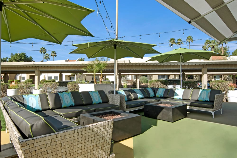 Eclectic outdoor seating area with sunshades and lounge chairs at Avia McCormick Ranch Apartments in Scottsdale, Arizona