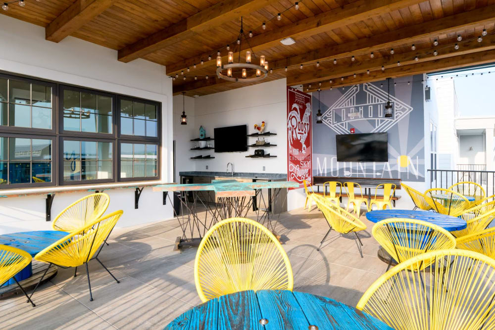 Covered outdoor space with kitchen pass-through, tables, and outdoor tv at Bluebird Row in Chattanooga, Tennessee