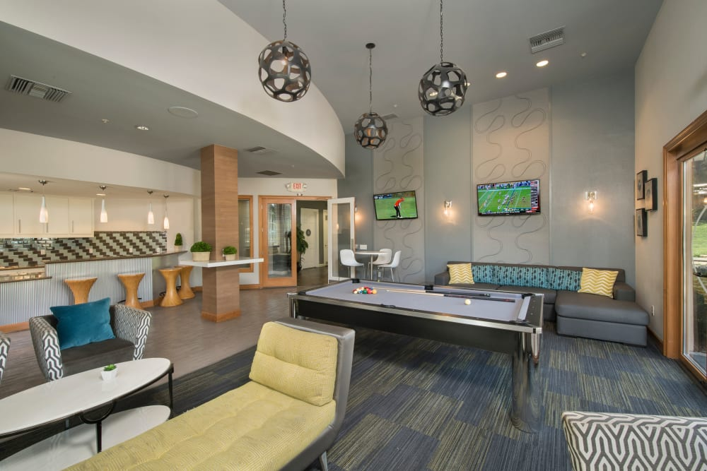 Resident clubhouse with plenty of seating for entertaining guests and a pool table at Esplanade Apartment Homes in Riverside, California