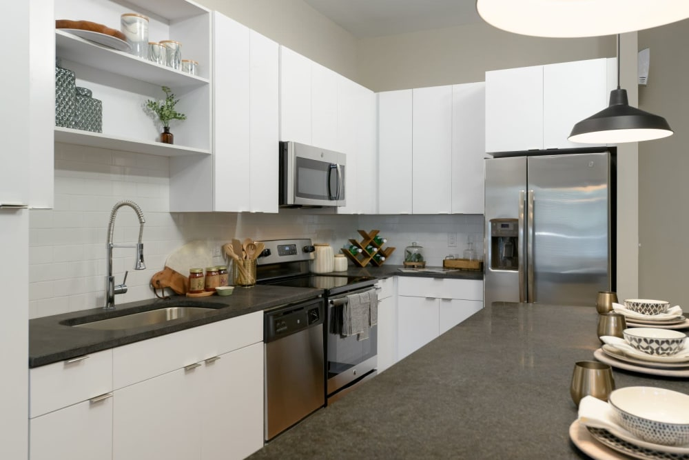 Kitchen with white cabinets, dark gray quartz counters, and stainless-steel appliances at Bluebird Row in Chattanooga, Tennessee