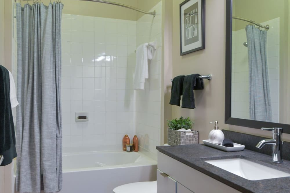 Bathroom with real tile shower, white cabinets, and dark gray quartz counters at Bluebird Row in Chattanooga, Tennessee