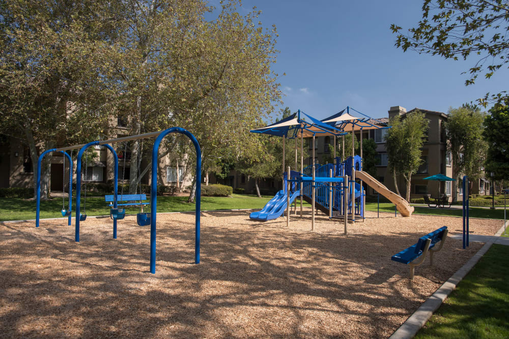 Children's playground with slides and swings at Esplanade Apartment Homes in Riverside, California