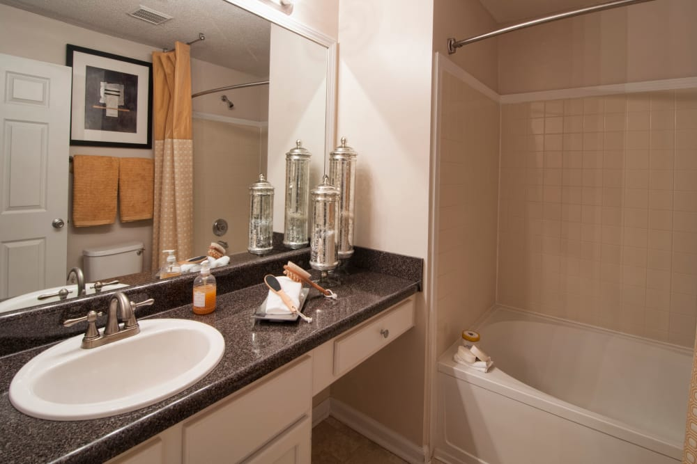 Bathroom vanity with large mirror and shower bathtub bathroom at Bellingham Apartment Homes in Marietta, Georgia