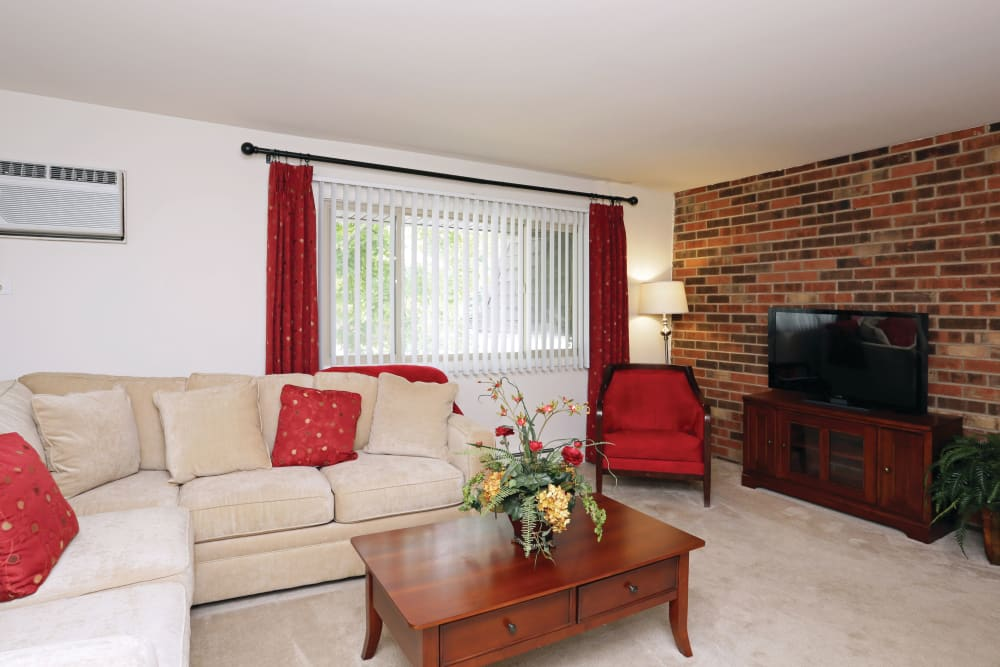 Living room featuring couch for comfortable seating and large windows for simple natural light in an apartment at Blackhawk Apartments in Elgin, Illinois