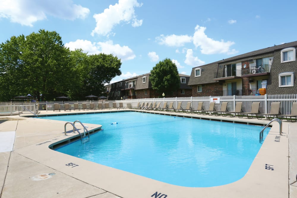 Community swimming pool with apartments in back as well as mature trees for shade at Blackhawk Apartments in Elgin, Illinois